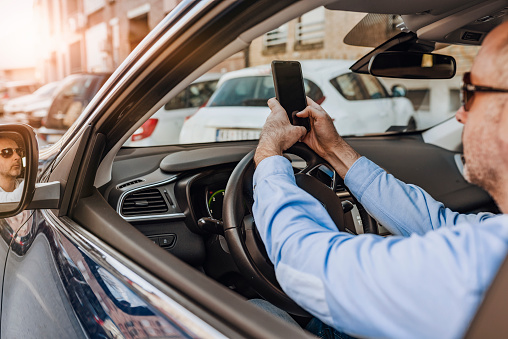 Driver with a smartphone in hand in the driver's seat.