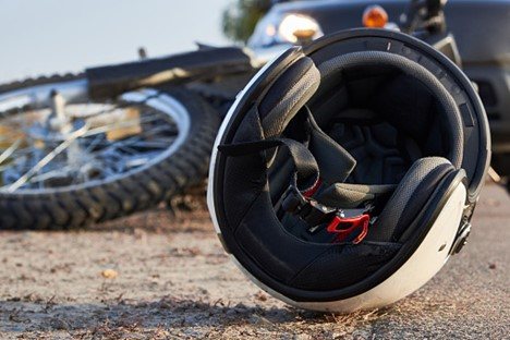 a helmet and motorcycle lying in the road with a pickup truck in the background