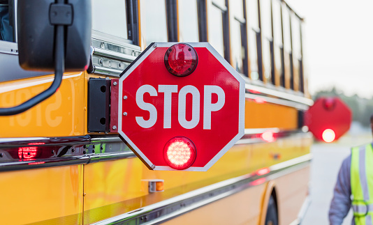 A yellow school bus stopped on the side of the road with stop signs out and flashing.