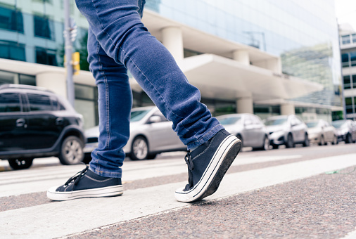 Close-up of the feet of a man in black sneakers crossing a street on the zebra or pedestrian path.